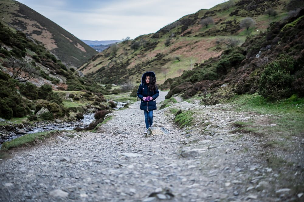Carding Mill Valley girl walking by stream