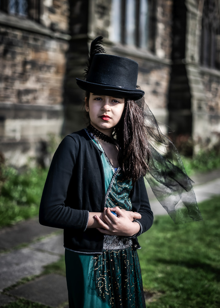 Girl portrait with top hat on chruch grounds