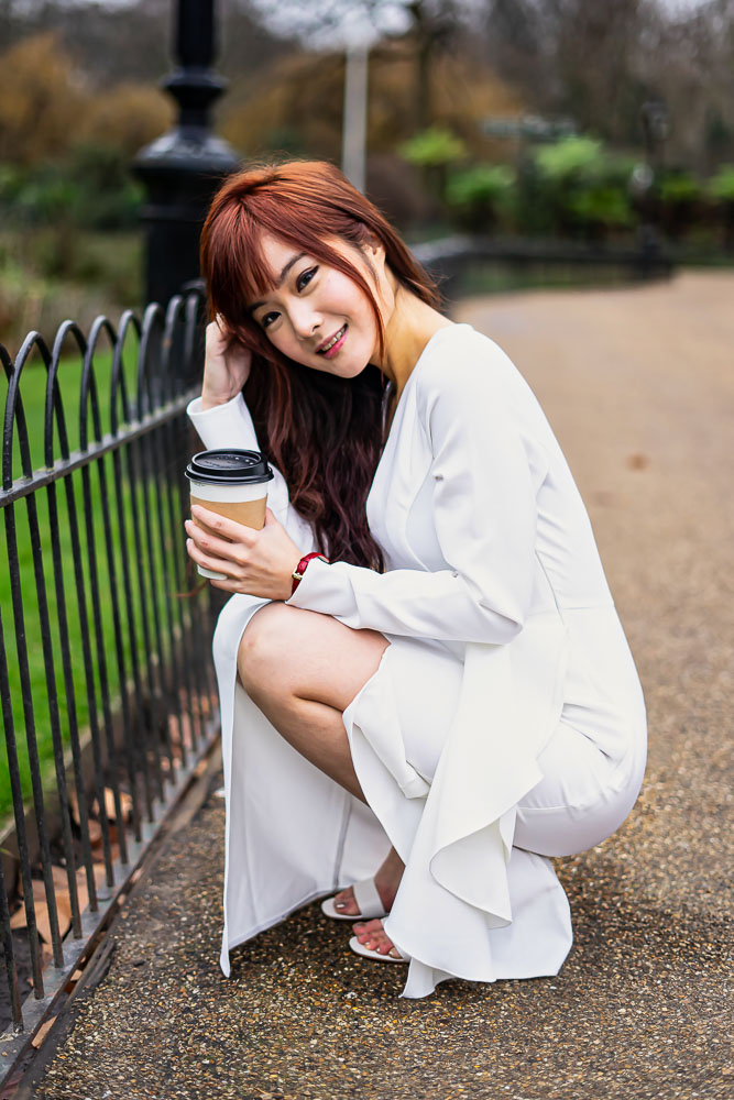 Portrait of a woman crouching holding a coffee in St James Parkm, Westminster, London
