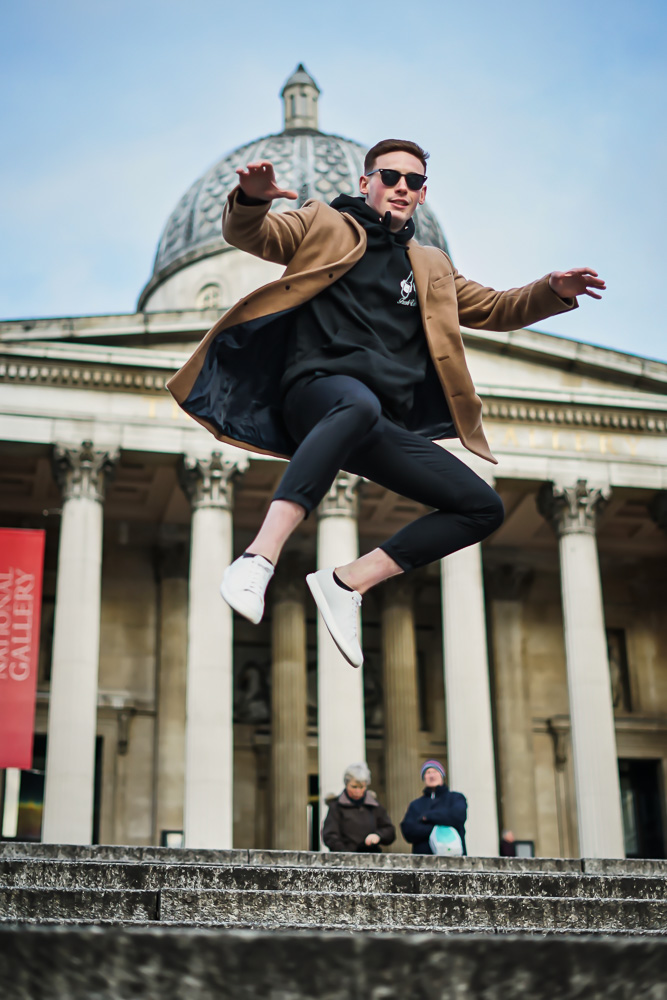 Levitation shot of man jumping in trafalgar square, London