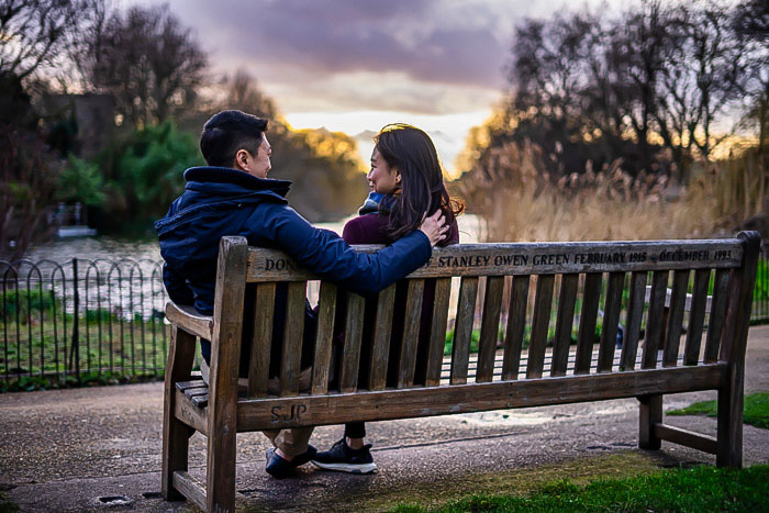 Romantic couple sat on the Stanley Owen Green Bench in St James Park, London