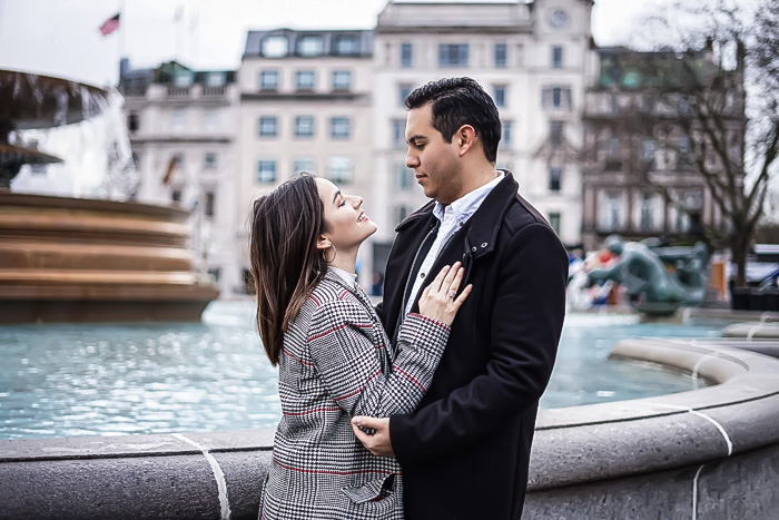 Portrait of romantic couple by fountains in Trafalgar Square, London